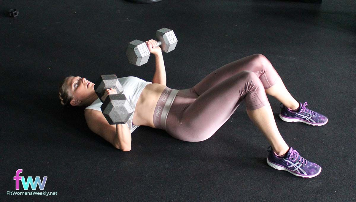 Holding 2 weights while laying on the ground for a chest press.
