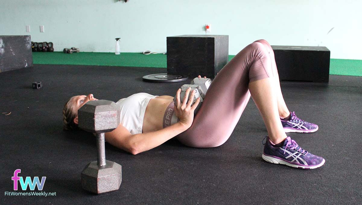 The bottom of a hip extension with a dumbbell over the hip bones.