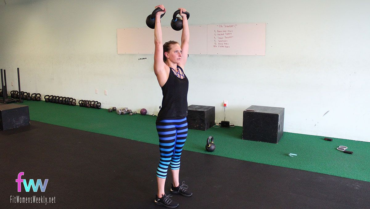 Top of prisoner squat. Reaching the kettlebells up high and core is engaged.