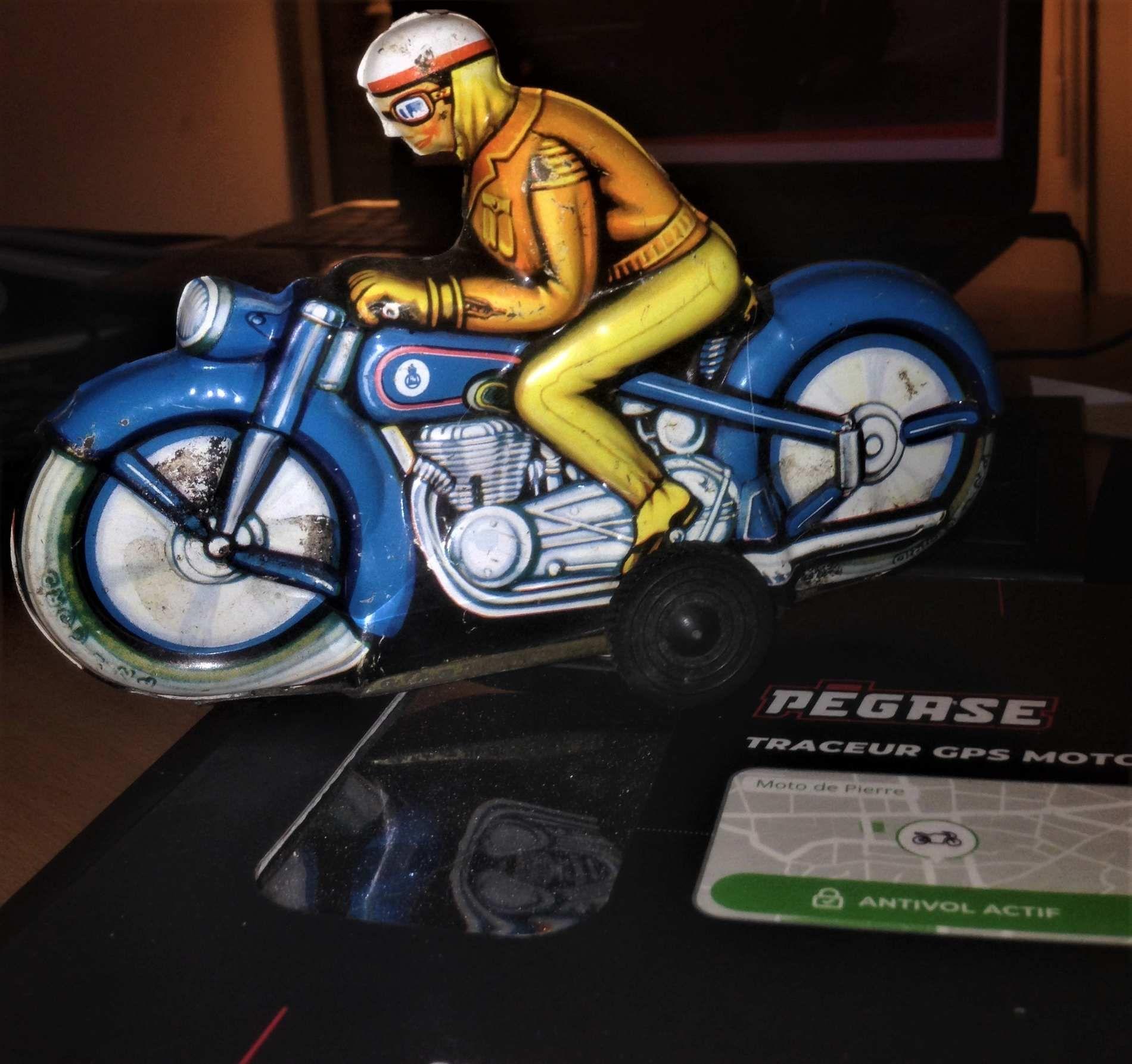 Un motard sur sa moto jouet à friction en fer blanc pour collectionneur