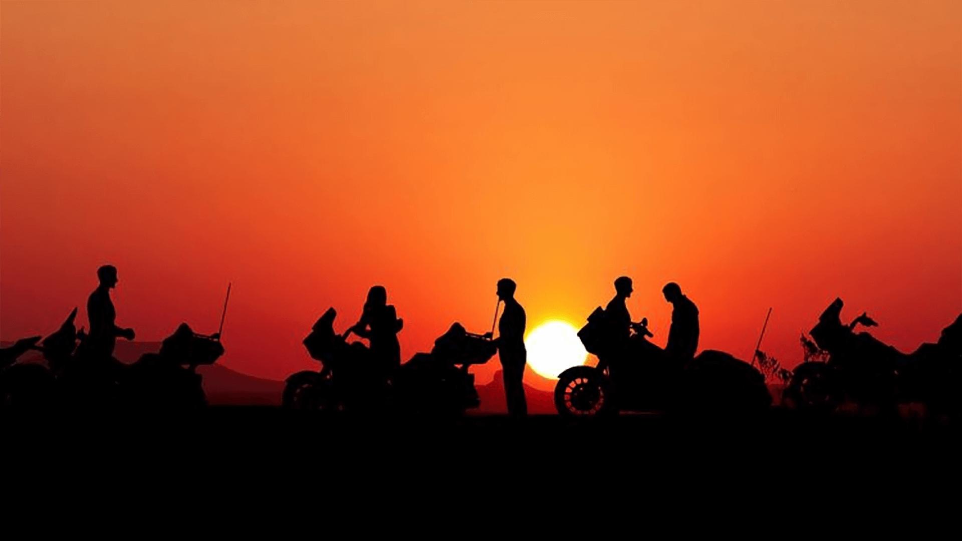 Des bikers en discussion proches de leurs motos devant un coucher de soleil