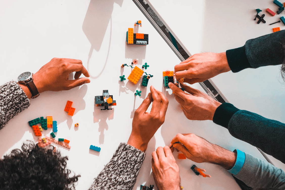 Two people putting together lego pieces
