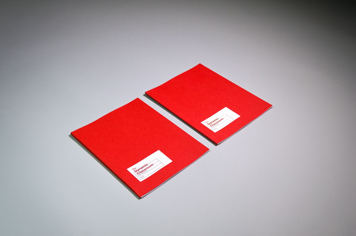 """Two copies of the book. It measures about 8 inches wide by 10.5 inches tall. The cover is bright red matte paper. A small white label is adhered towards the bottom left corner. On it is printed a small black table of information, with """"The Dynamic Classroom"""" overprinted in large red letters."""