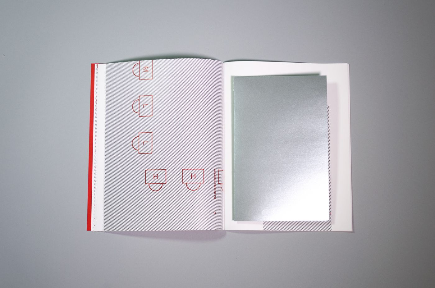 A folded poster printed on silver paper sits in the center of the book.