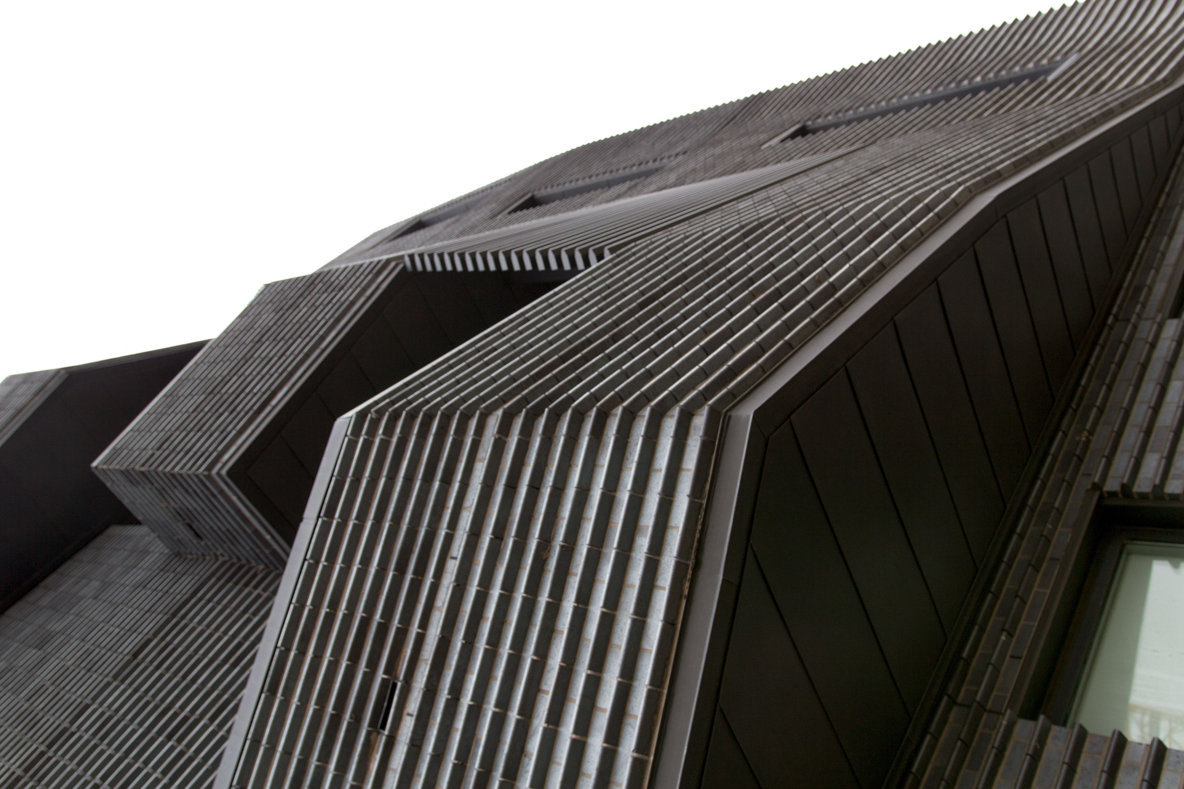 A modern black brick building, photographed at an angle that makes it unclear which way is up.
