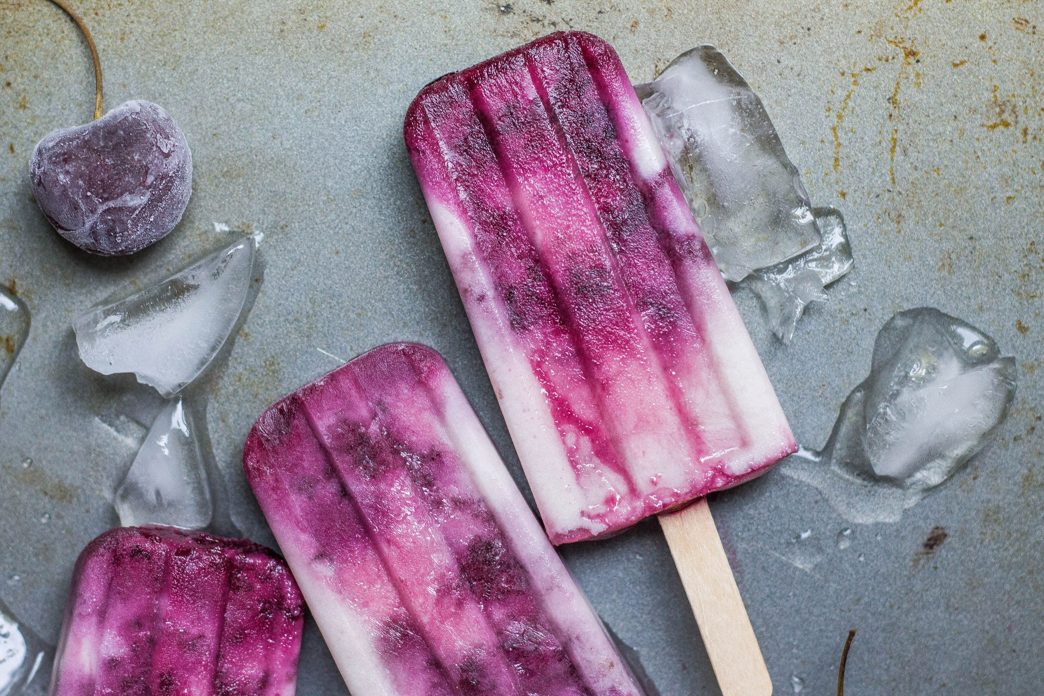 Three Queen Garnet yoghurt swirl popsicles sitting on a table, with glass and frozen berries alongside