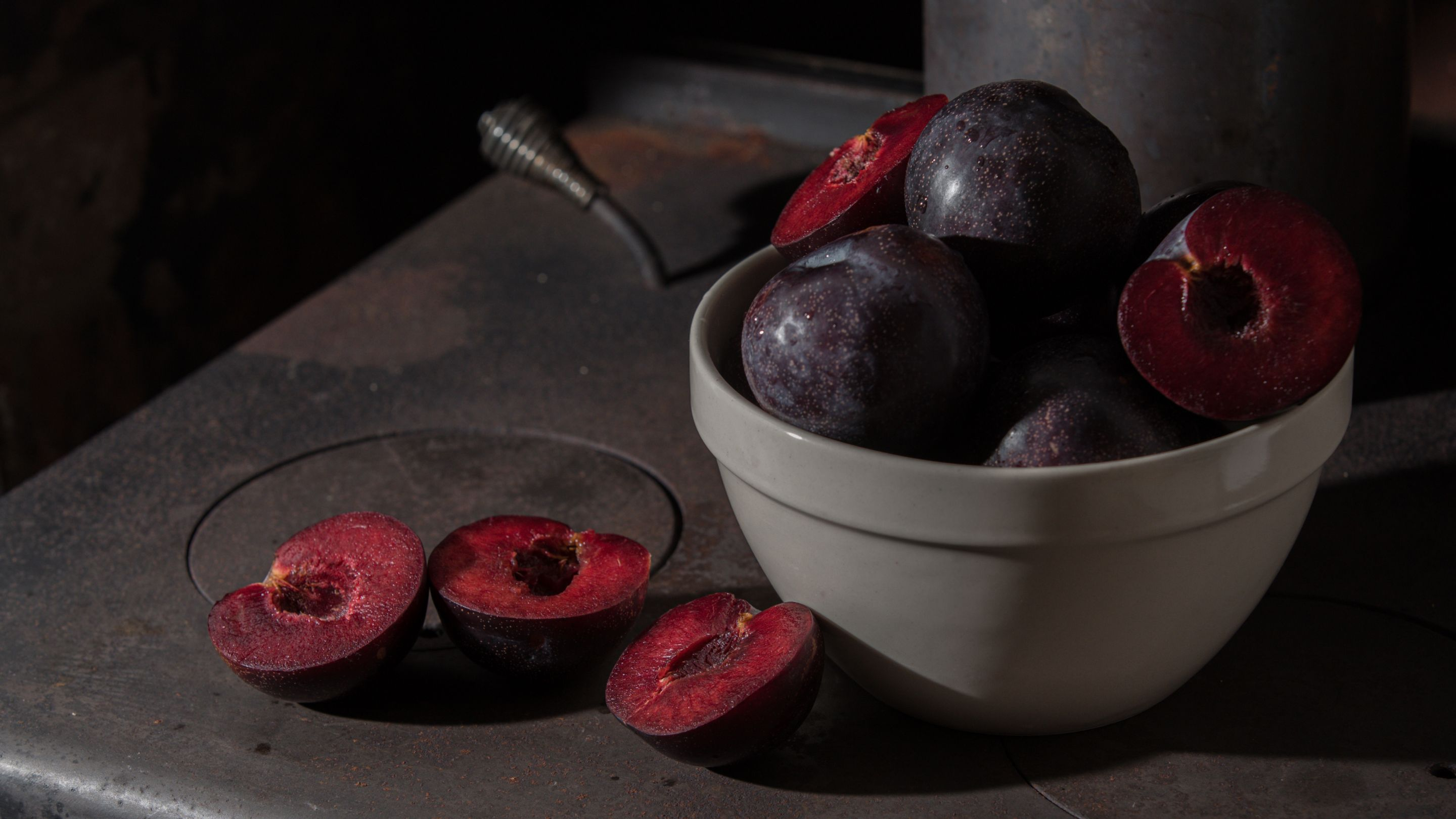 A bowl of ripe Queen Garnet plums, with Queen Garnet plums sliced in half beside the bowl