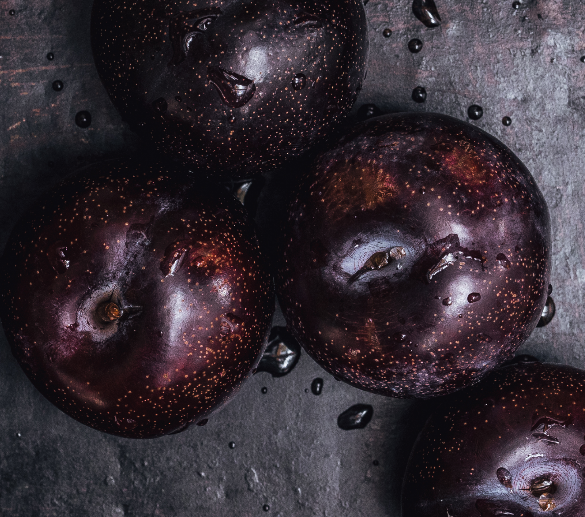 Four Queen Garnet plums sitting on a wooden bunch, with water droplets glistening around and on the fruit