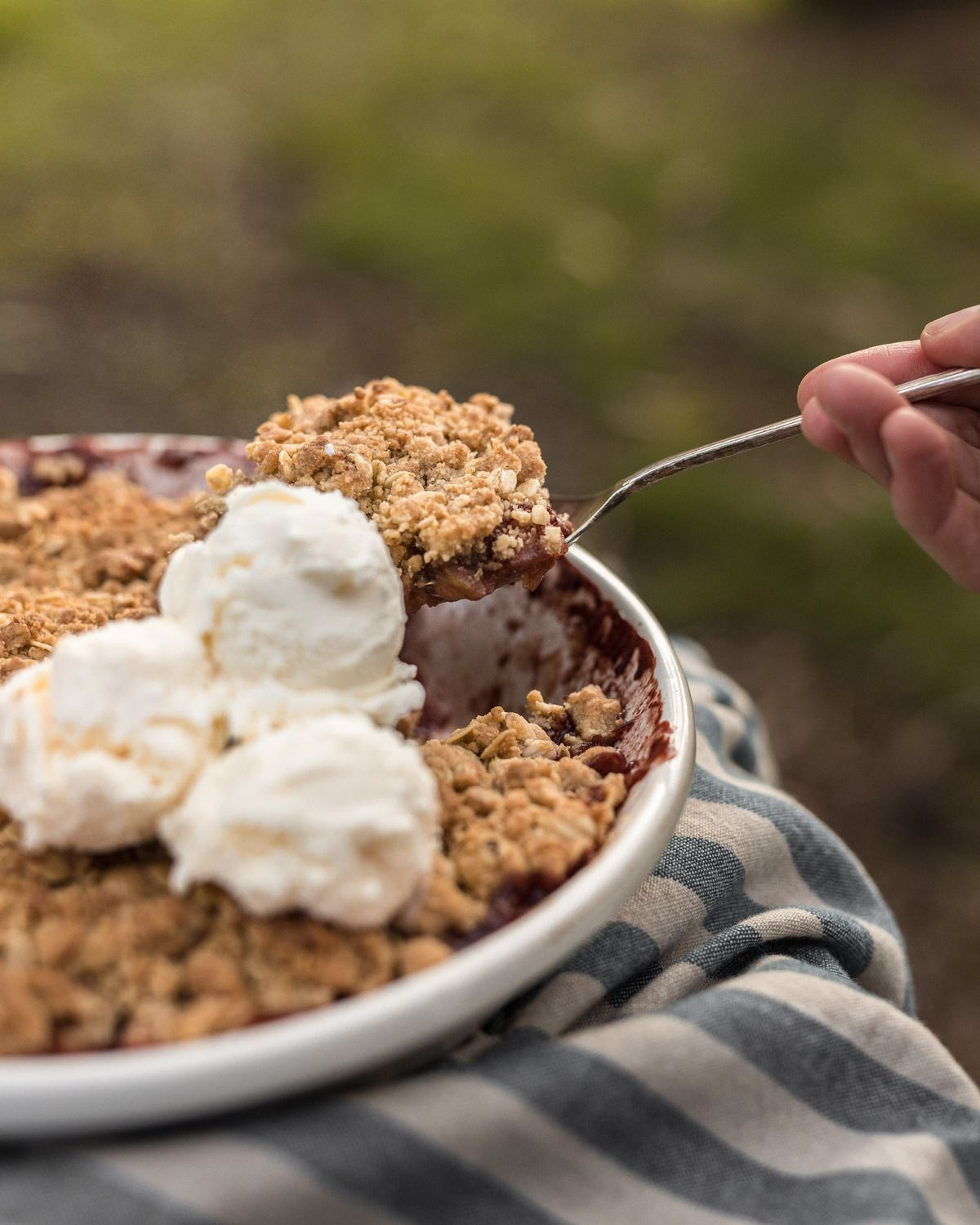 Plum + Apple Crumble topped with cream being spooned out to serve