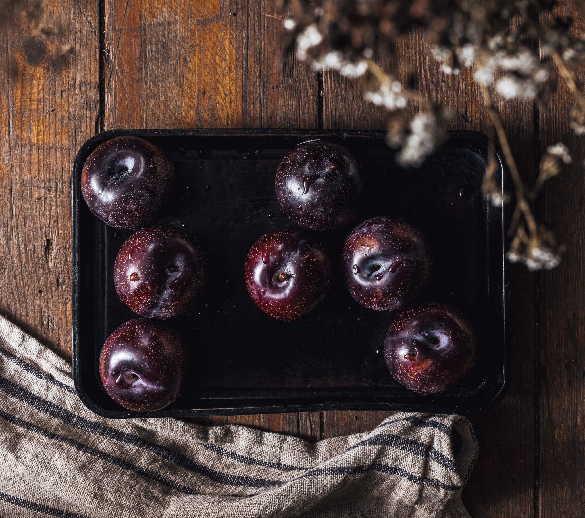 A group of Queen Garnet plums sitting on a wooden table