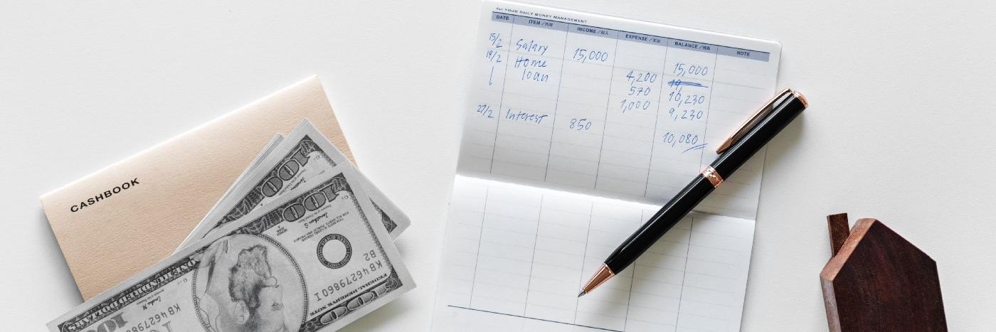 Des billets et un carnet sur comment investir son argent