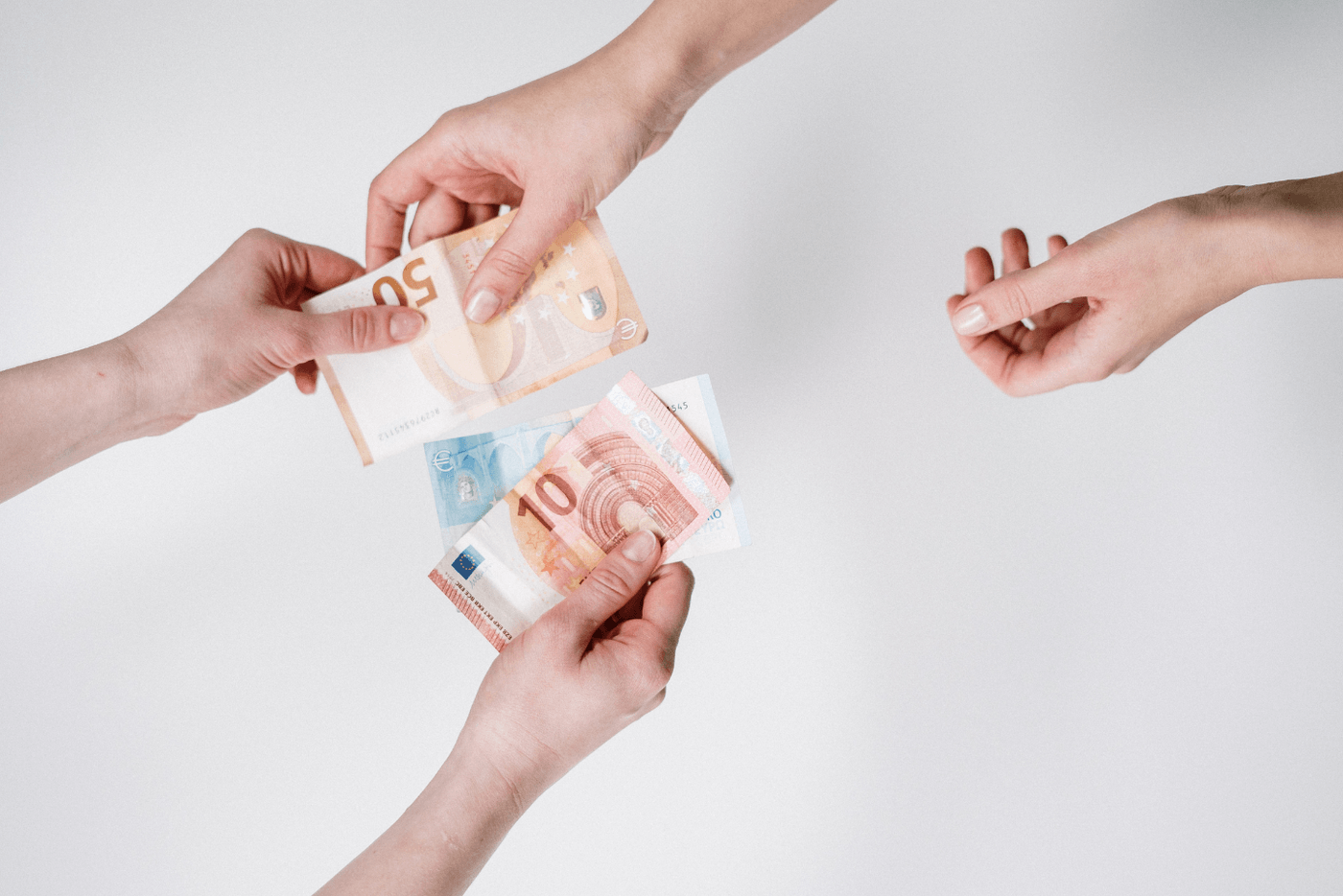 Deux mains qui s'échangent des billets en euro