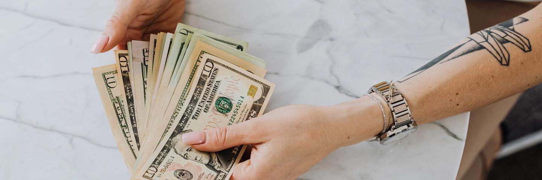 Une personne tient des billets dans ses mains