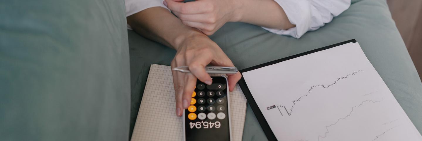 Une femme calcule des frais sur une calculatrice