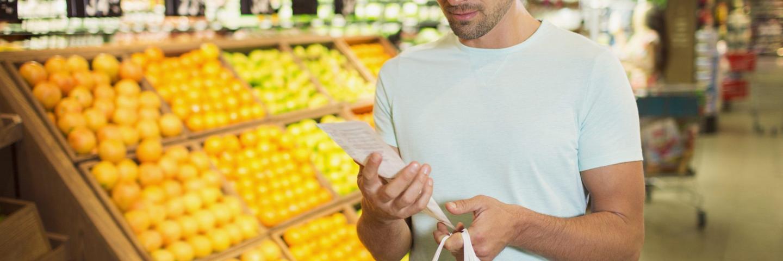 Un homme regarde son ticket de caisse pour faire des économies sur les courses
