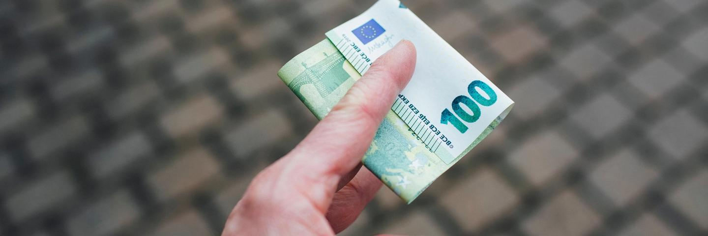 Des billets de 100 euros dans une main