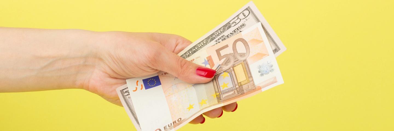 Une main qui tient des billets euros et dollars