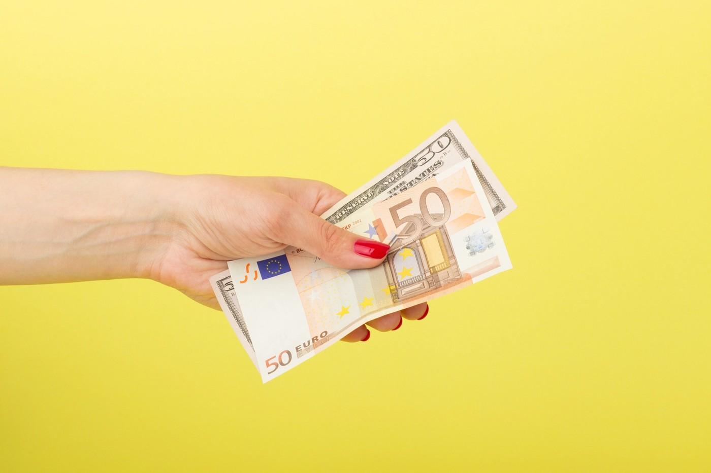 Une personne qui tend des billets de banque