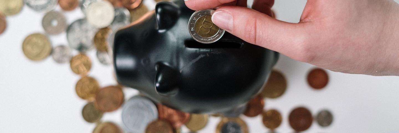 Une main met des euros dans une tirelire