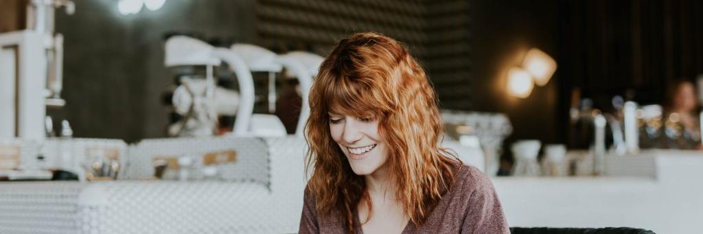 Une femme assise dans un café en train de sourire