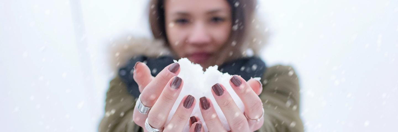 Une femme avec une boule de neige dans les mains