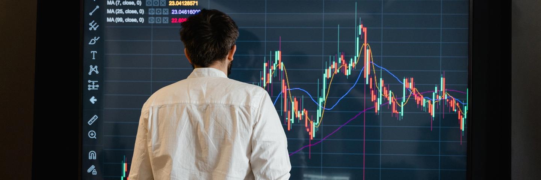 Un homme devant un écran pour acheter des actions