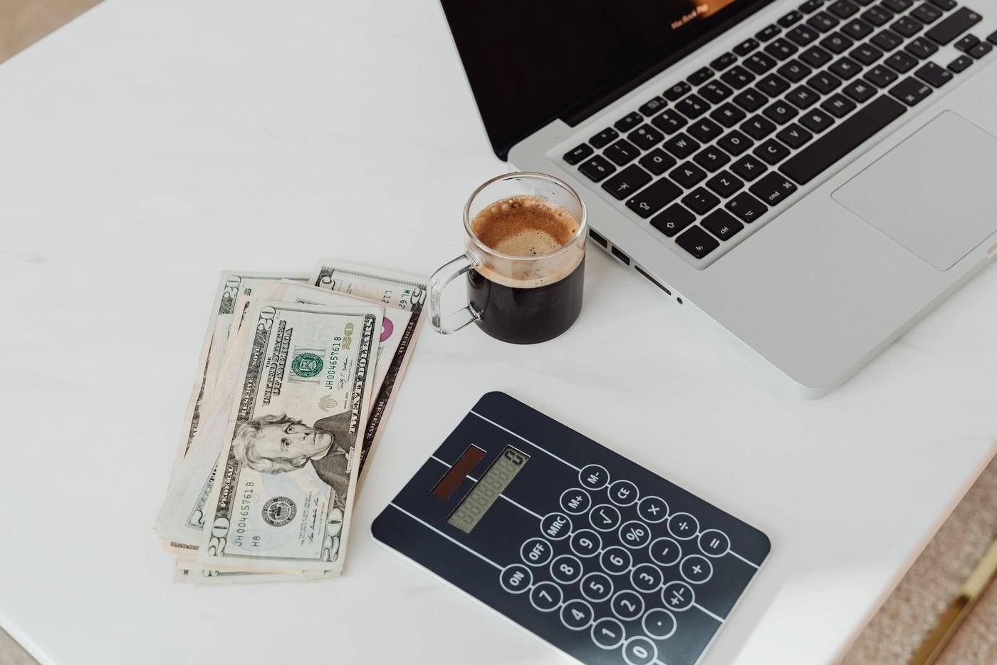 Des billets posés sur une table avec une calculatrice