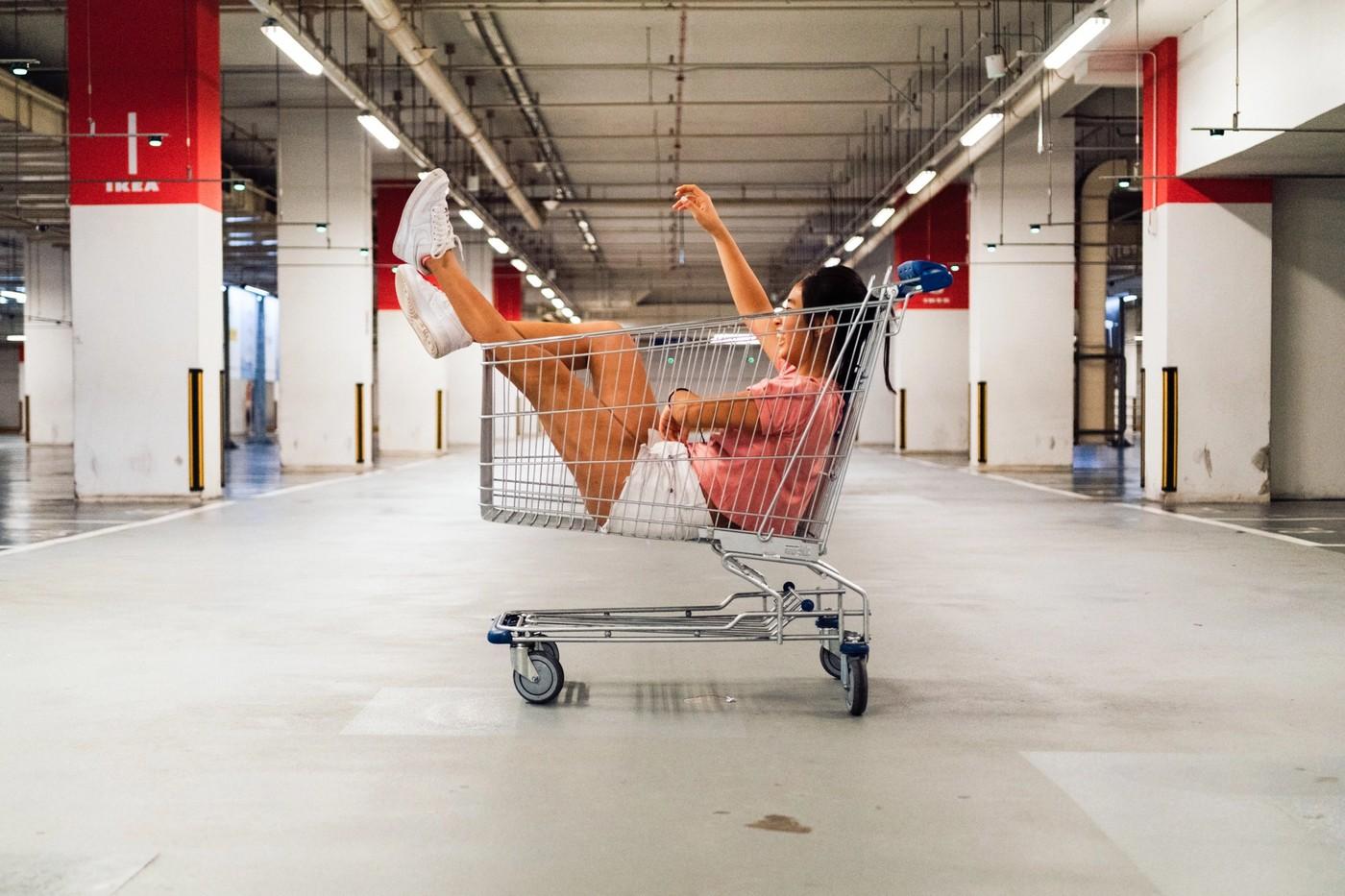 Une femme dans une caddie de supermarché