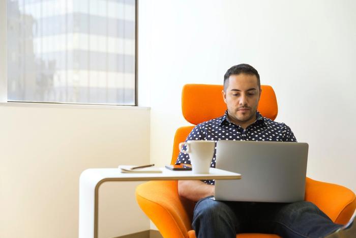 Un homme en train de travailler à domicile sur une chaise de bureau