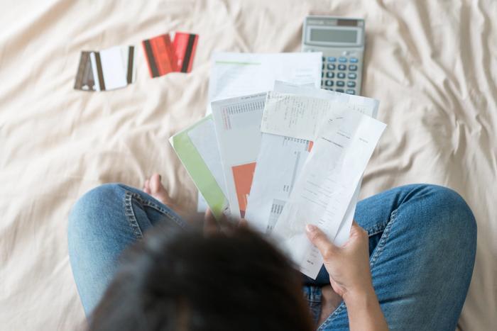 Une femme tient dans sa main des lettres d'impôts