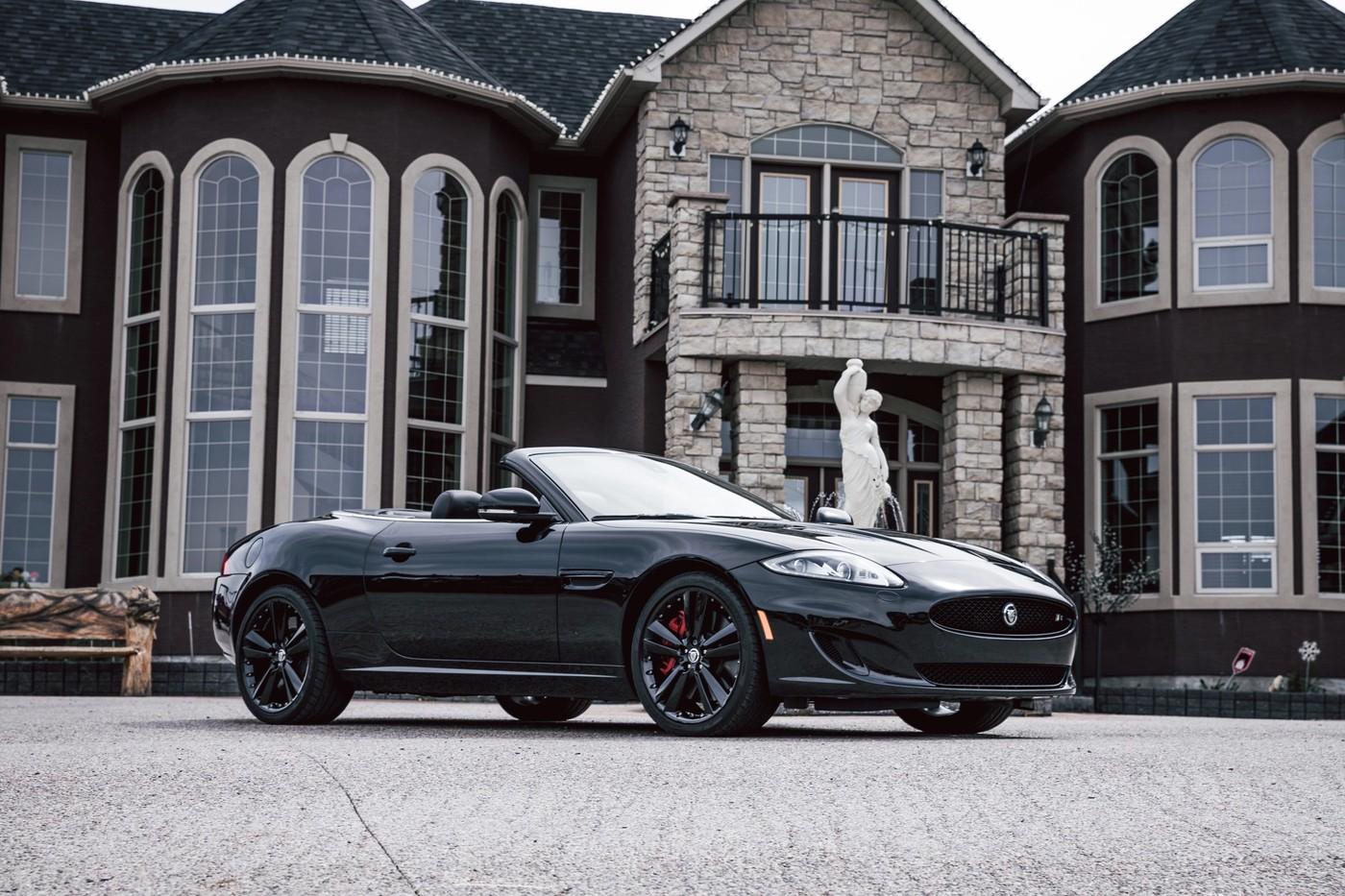 Une voiture de luxe devant une grande maison