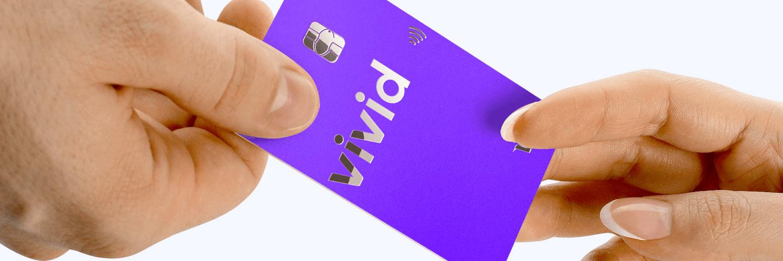 Deux mains tiennent une carte Vivid Money