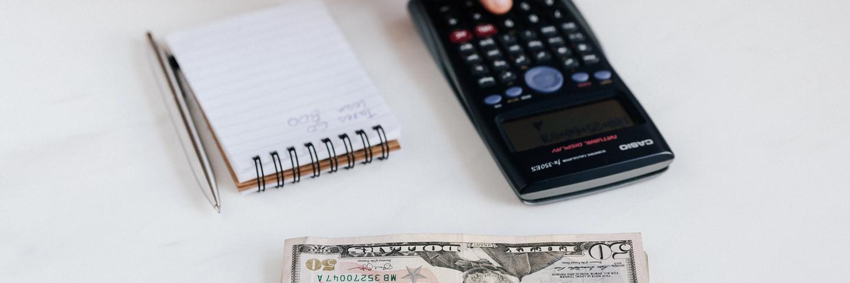 Une calculette et des dollars sur une table