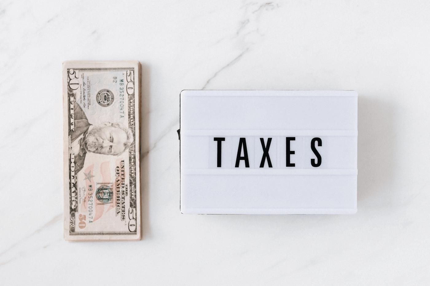 Un signe taxes à côté de billets de banque