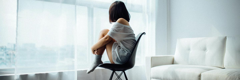 Une femme assise devant une fenêtre