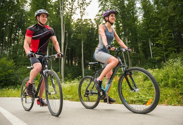 Couple of cyclists on affordable hybrid bikes