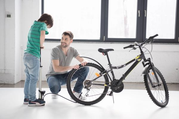 Father and son busy pumping a bike's tires