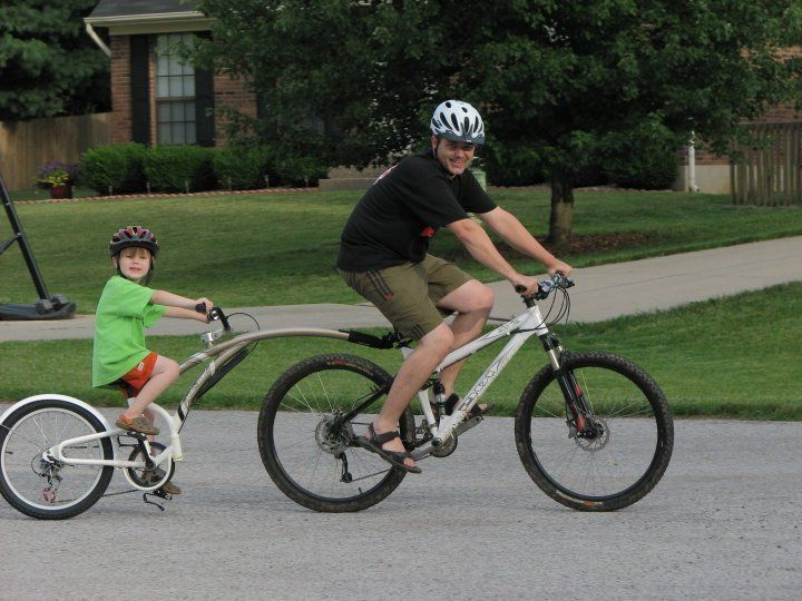 Father and son on a bike tandem attachment