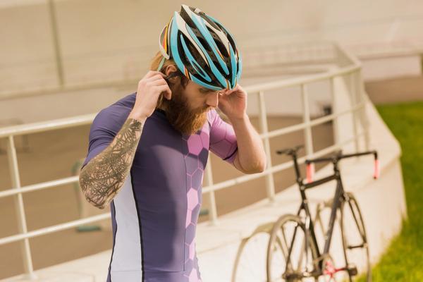 Road biker putting his helmet on