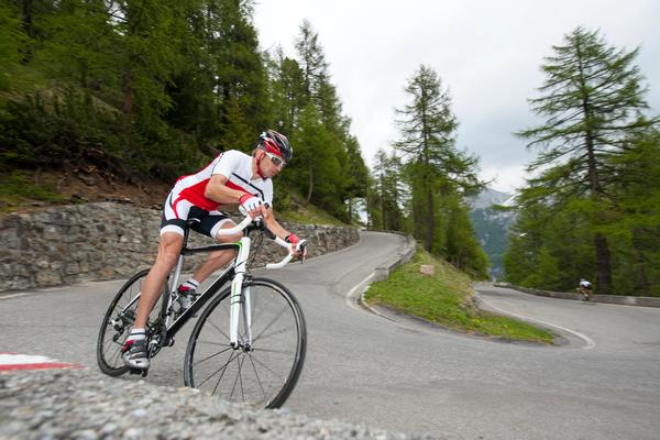 Man riding road bicycle down hill