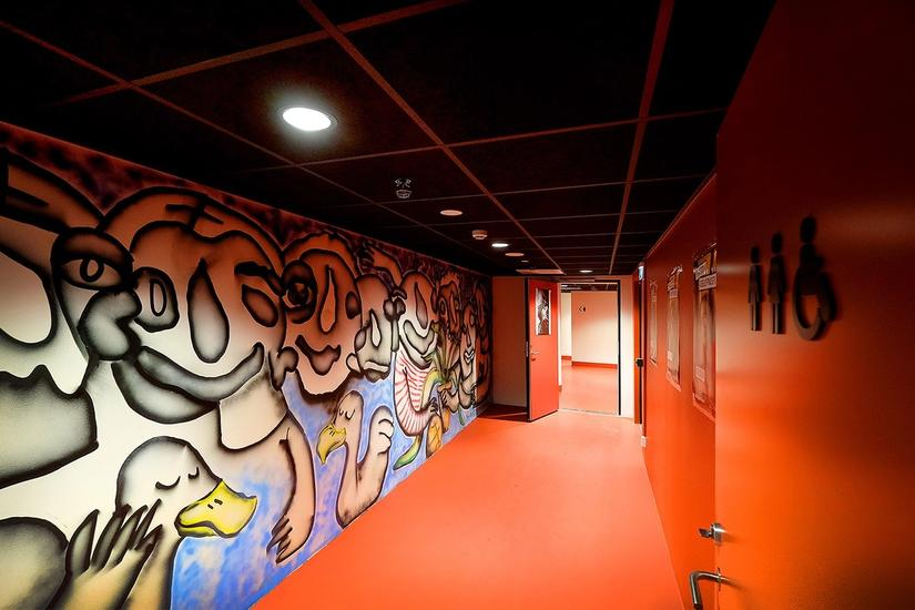 photo of red hallway with spray painted art on the left wall