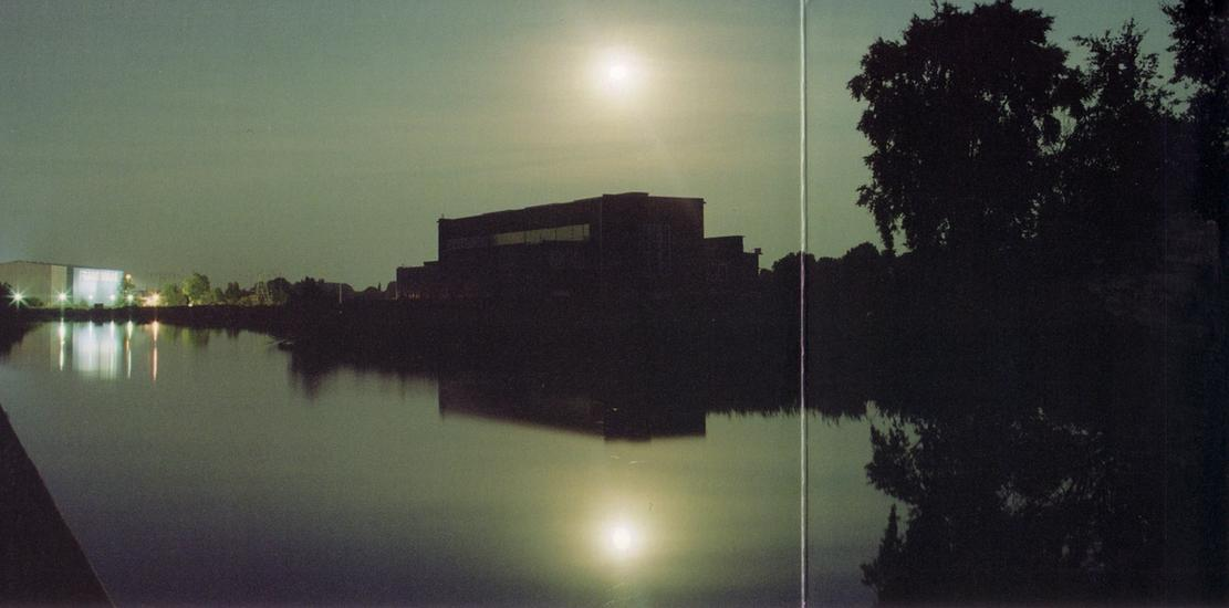 High contrast photo of lake reflecting the sun over a building.