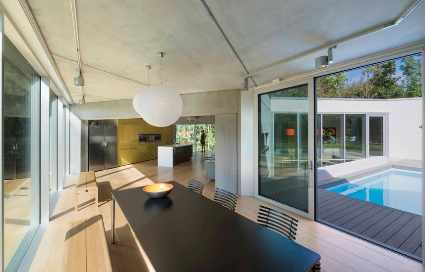 Dining area with glass windows and door open towards pool area