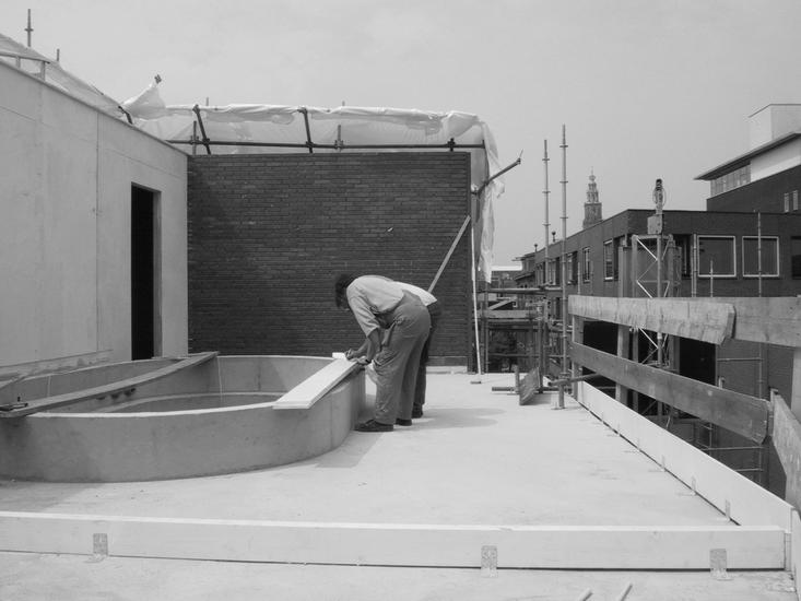 black and white photo of the building of the swimming pool on the third floor