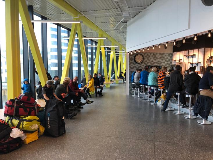 Photo of entrance hall with yellow pillars, benches and a cafe