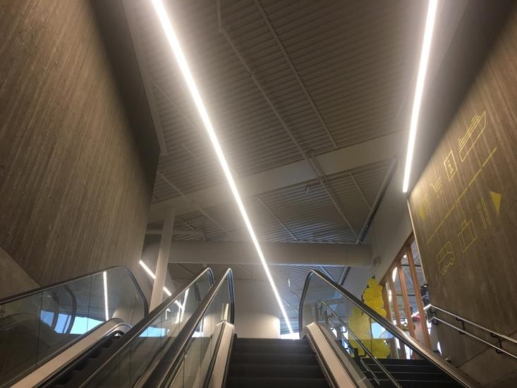 Escalator up to entrance hall with  fluorescent lighting