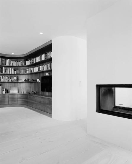 The rooms are connected through a fireplace integrated into the wall, creating a void with a view through from both sides. A custom-made bookshelf also reinforces the distinction between the different spaces.