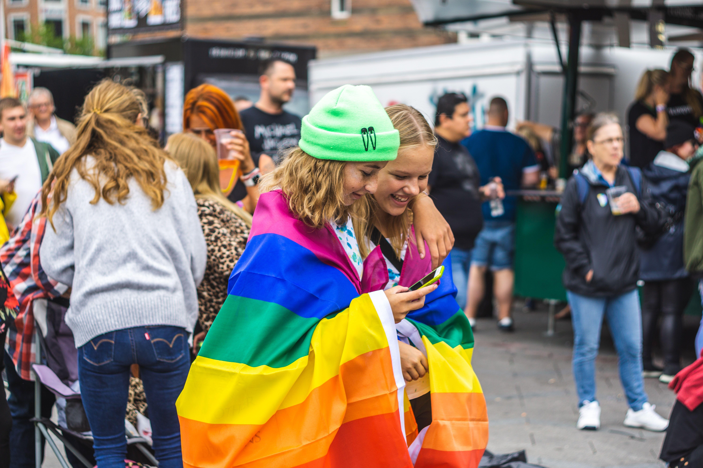 To jenter som har et regnbueflagg surret rundt seg