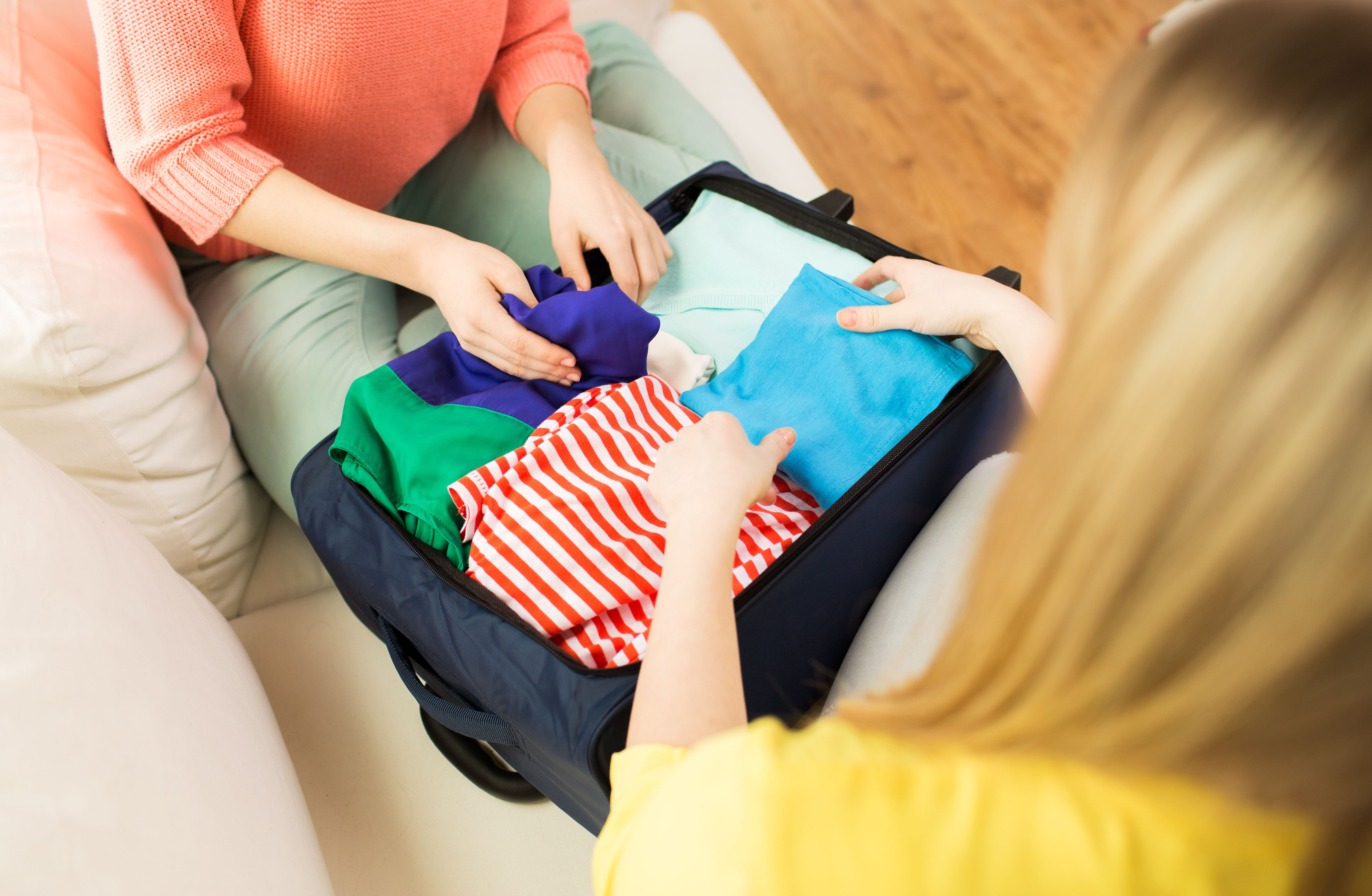 Jente som får hjelp av moren sin til å pakke en koffert.