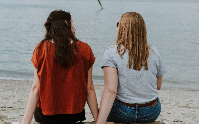 To jenter som sitter på en stubbe på en strand som snakker sammen. Foto: Unsplash / Priscilla Preez